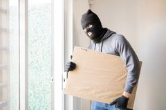 Male criminal stealing some art. Burglar wearing a ski mask and gloves getting away with a stolen piece of art royalty free stock image