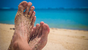 Male Cross Feet at the Sandy Beach, Ocean in Background, Bali. Indonesia Royalty Free Stock Photo