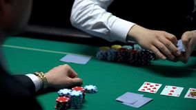 Male croupier dealing cards for businessman poker player, hoping for good hand. Stock photo royalty free stock images