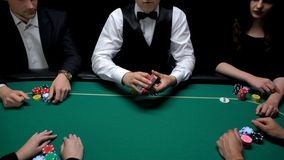 Male croupier holding cards ready to start poker game at casino, gambling sports stock photos