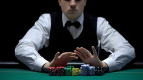 Male croupier moving chips into camera, gambling business, chance to win money. Stock photo stock photos