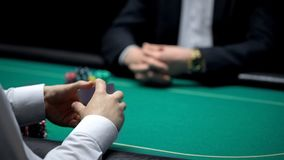 Male croupier shuffling cards at casino, ready to start poker game with client. Stock photo stock photo