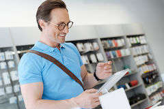 Male customer beaming while looking at digital tablet at store. I am in disbelief. Brown haired man wearing glasses smiling while holding and testing a template Stock Image