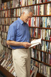 Male customer in bookshop. Reading a book Stock Image
