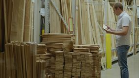 Male customer chooses wooden boards in hardware store. Hardware store, racks, shop of building materials and tools, male buyer chooses the instruments, young man stock video