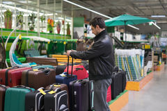 Male customer choosing travel suitcase. In the supermarket Royalty Free Stock Images