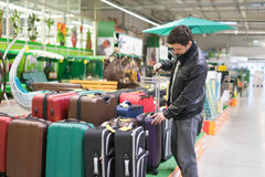 Male customer choosing travel suitcase. In the supermarket. He is holding handle Stock Images