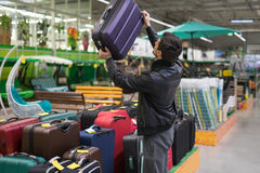 Male customer choosing travel suitcase. In the supermarket. He picked up the bag Stock Photography