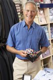 Male customer in clothing store. Holding a tie and smiling at camera Royalty Free Stock Image