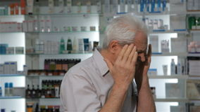 Male customer comes to the drugstore with headache stock video