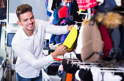 Male customer examining knit caps in sports store Royalty Free Stock Photo