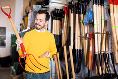 Male customer examining pitchforks Royalty Free Stock Photography