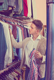 Male customer examining shirts in men's cloths store Royalty Free Stock Image