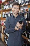 Male Customer Holding Wine Bottle By Shelves. Portrait of smiling young male customer holding wine bottle by shelves in store Stock Image