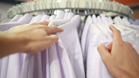 Male customer looking for T-shirts in a fashion store stock footage