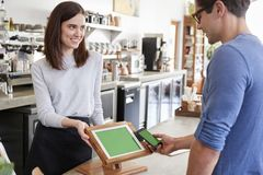 Male customer makes payment by smartphone at a coffee shop stock photography
