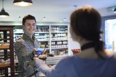 Male Customer Making Contactless Payment For Shopping Using Mobile Phone In Delicatessen stock photo