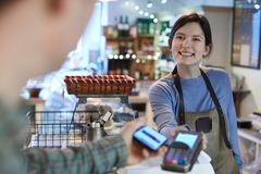 Male Customer Making Contactless Payment For Shopping Using Mobile Phone In Delicatessen royalty free stock photos