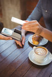 Male customer paying with smartphone. At coffee shop Royalty Free Stock Image