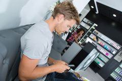 Male customer with phone waiting at hair salon. Man Stock Images