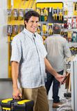 Male Customer Purchasing Tools At Shop. Portrait of smiling male customer purchasing tools with men in background at hardware shop Royalty Free Stock Photo