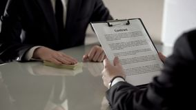 Male customer reading loan contract, bank employee holding money, mortgage. Stock photo stock images