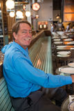 Male customer at a restaurant. Caucasian male sitting at a restaurant, smiling Royalty Free Stock Images