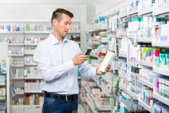 Male Customer Scanning Product Through Mobile. Mid adult male customer scanning product through mobile phone in pharmacy Stock Image