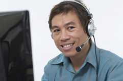 Male customer service representative. Asian business man wearing headset and smiling Stock Photography