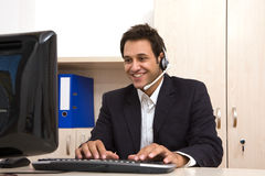 Male customer service representative. At the office with computer Stock Image