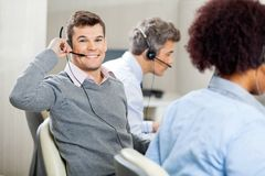 Male Customer Service Representative Using Headset. Portrait of young smiling male customer service representative using headset while colleagues working in Stock Image