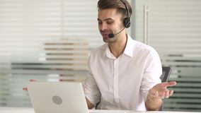 Telemarketer wearing headset looking at laptop make business video call