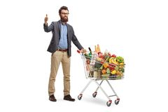 Male customer with a shopping cart giving thumbs up. Full length portrait of a male customer with a shopping cart giving thumbs up isolated on white background royalty free stock images