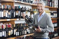 Male Customer Shopping For Wine Bottles In Store. Portrait of mature male customer shopping for wine bottles in store Royalty Free Stock Photography
