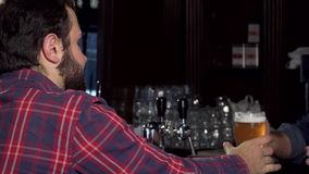 Male customer smiling to the camera, having delicious beer at the pub stock footage