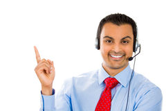Male customer support member pointing at a copy space. A portrait of a male customer support member pointing at a copy space Royalty Free Stock Photography
