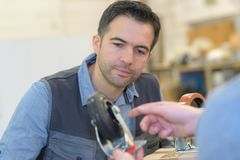 Male customer talking with technician about wheel in work shop. Wheel Stock Photography