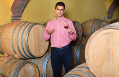 Male customer tasting red wine from wooden barrels. Cheerful  male customer tasting red wine from wooden barrels in factory Stock Images