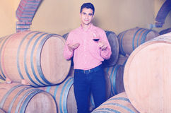 Male customer tasting red wine from wooden barrels. Cheerful  male customer tasting red wine from wooden barrels in factory Royalty Free Stock Photos