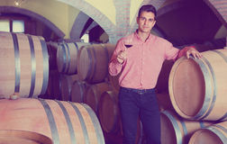 Male customer tasting red wine from wooden barrels. Glad cheerful smiling male customer tasting red wine from wooden barrels in factory Royalty Free Stock Photos