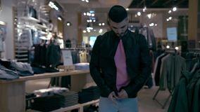 Male Customer Trying Out Leather Jacket. Man Shopping for Clothing in Store stock video footage