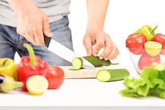 Male cutting cucumber, preparing salad Royalty Free Stock Photo