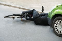 Male cyclist after car accident on road Royalty Free Stock Photo