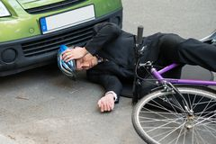 Male cyclist after car accident on road. Unconscious Male Cyclist Lying On Road After Road Accident Royalty Free Stock Image