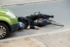 Male cyclist after car accident on road. Unconscious Male Cyclist Lying On Road After Road Accident Stock Images