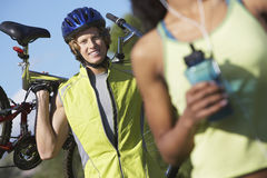 Male Cyclist Carrying Bicycle With Woman In The Foreground Stock Photography