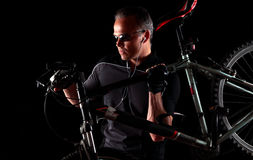 Male cyclist carrying mountain bike. Fit, male mountain biker carrying bike in dark Royalty Free Stock Photo