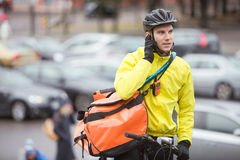 Male Cyclist With Courier Bag Using Mobile Phone. Young male cyclist with courier delivery bag using mobile phone on street Stock Image
