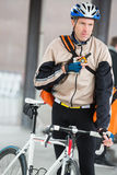 Male Cyclist With Courier Bag Using Walkie-Talkie Stock Photography