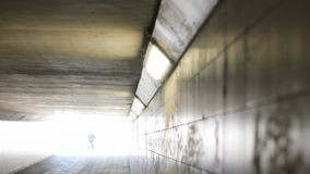 Male Cyclist Cycling into the Light at the End of the Tunnel. Static medium long high angle shallow depth of field shot of a hooded male cyclist with baggage stock footage